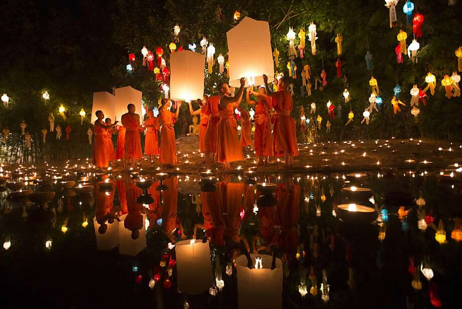 Misfortune drifts away:Buddhist monks release lit lanterns during the Loy Krathong Festival at a temple in Chiang Mai, Thailand. The monks launch the lanterns and float candles in lotus-shaped baskets into ponds and rivers in order to   cast away their bad luck. Photo: Vincent Thian, Associated Press