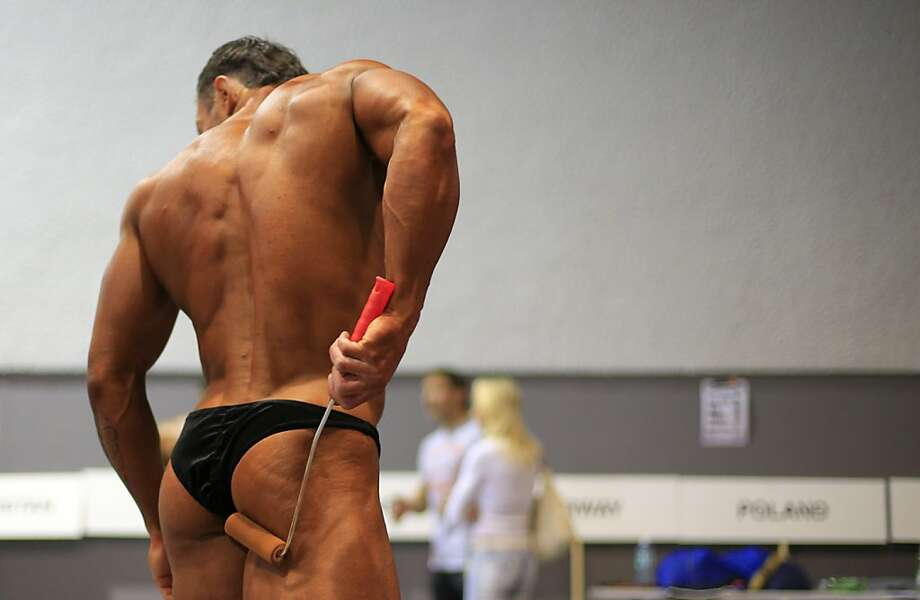 No, they don't use tanning booths:A contestant at the World Classic Bodybuilding Championship and Bikini Fitness World Cup in St. Polten, Austria, adds a little color to his cheeks. Photo: Alexander Klein, AFP/Getty Images