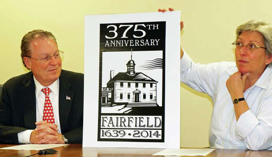 First Selectman Mike Tetreau and Amy Mezoff show off the log for the town's 375th anniversary that Mezoff designed. Photo: Genevieve Reilly / Fairfield Citizen