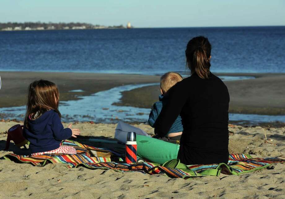 Sofie Kvaal and her children, Karen and Martin enjoy some snacks at Greenwich Point Beach in Greenwich, Conn. on Monday, Nov. 18, 2013. Plenty of people headed out to the park to enjoy the summer-like weather with a high temperature reaching the mid-60's. Tuesday is expected to be quite a bit cooler, in the mid-40's. Photo: Cathy Zuraw / Greenwich Time