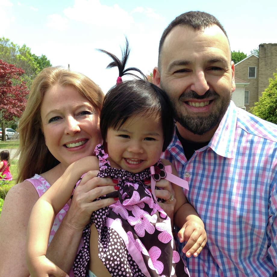 Nancy and Mike Lombardo, of Fairfield, with their 2 1/2-year-old daughter Tammy Lee Yu Lombardo at the National Adoption Month ceremony, in Hartford, on Monday. Photo: Ned Gerard, Contributed Photo / Connecticut Post contributed