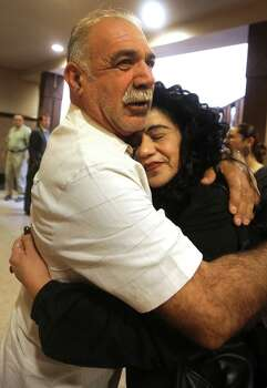 Margaret Rivera, right, mother of Cassandra Rivera, is hugged by Jessie Rivera, as family and friends of Elizabeth Ramirez, Cassandra Rivera and Kristie Mayhugh gather in the 175th District Court in the Cadena Reeves Justice Center to hear that the 3 women  will be released from prison. Monday, Nov. 18, 2013. The fourth women, Anna Vasquez, was released on parole from prison just over a year ago. Photo: Bob Owen, San Antonio Express-News / ©2013 San Antonio Express-News