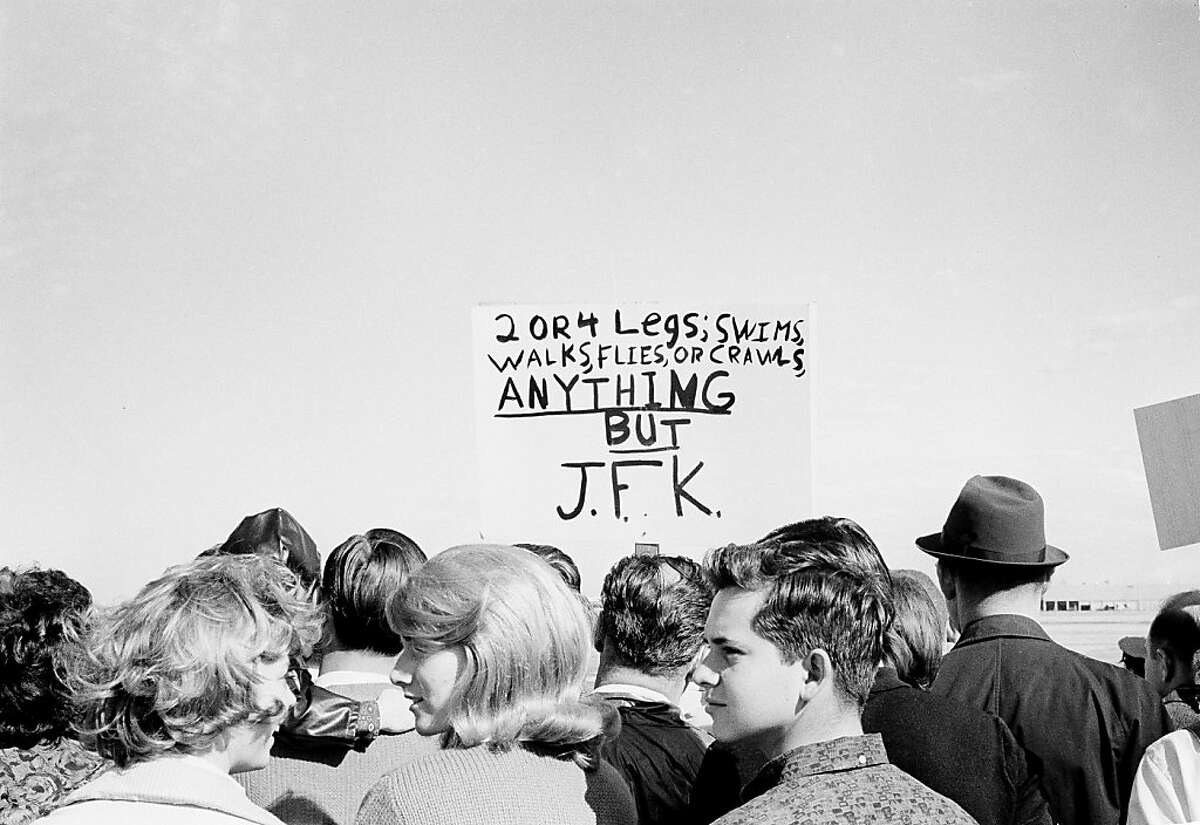 Anti-Kennedy protesters with placards are seen among the throngs of supporters that came out to Love Field in Dallas, Tex., to see the president arrive, Nov. 22, 1963. (AP Photo)