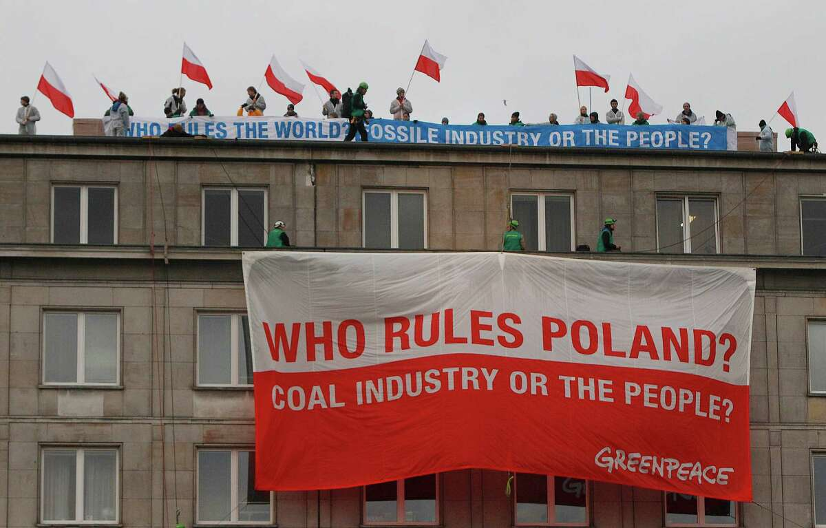 Climate activists with protest banners wave polish flags on the rooftop of the Economy Ministry in Warsaw, Poland Monday, Nov. 18, 2013. They went up the rooftop to protest a coal conference opening to coincide with U.N. talks on preventing global warming, that is also the result of greenhouse gases coming from burning coal. (AP Photo/Czarek Sokolowski) ORG XMIT: XCS153