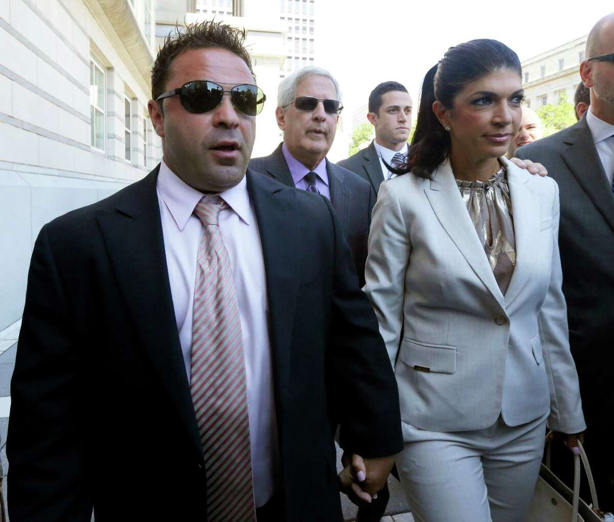 """FILE - In this July 30, 2013 file photo, ?""""The Real Housewives of New Jersey?"""" stars Giuseppe """"Joe"""" Giudice, left, and his wife, Teresa Giudice, of Montville Township, N.J., walk out of Martin Luther King Jr. Courthouse after an appearance in Newark, N.J. The Giudices are facing additional fraud charges as they were each indicted Monday, Nov. 18, 2013, on one count of bank fraud and one count of loan application fraud. Monday's charges are in addition to a 39-count indictment handed down in July, charging the couple with conspiracy to commit mail and wire fraud, bank fraud, making false statements on loan applications and bankruptcy fraud. (AP Photo/Julio Cortez, File) ORG XMIT: NY118"""