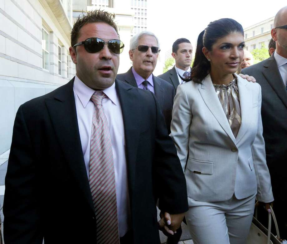 "FILE - In this July 30, 2013 file photo, ""The Real Housewives of New Jersey"" stars Giuseppe ""Joe"" Giudice, left, and his wife, Teresa Giudice, of Montville Township, N.J., walk out of Martin Luther King Jr. Courthouse after an appearance in Newark, N.J. The Giudices are facing additional fraud charges as they were each indicted Monday, Nov. 18, 2013, on one count of bank fraud and one count of loan application fraud. Monday's charges are in addition to a 39-count indictment handed down in July, charging the couple with conspiracy to commit mail and wire fraud, bank fraud, making false statements on loan applications and bankruptcy fraud. (AP Photo/Julio Cortez, File) ORG XMIT: NY118 Photo: Julio Cortez / AP"