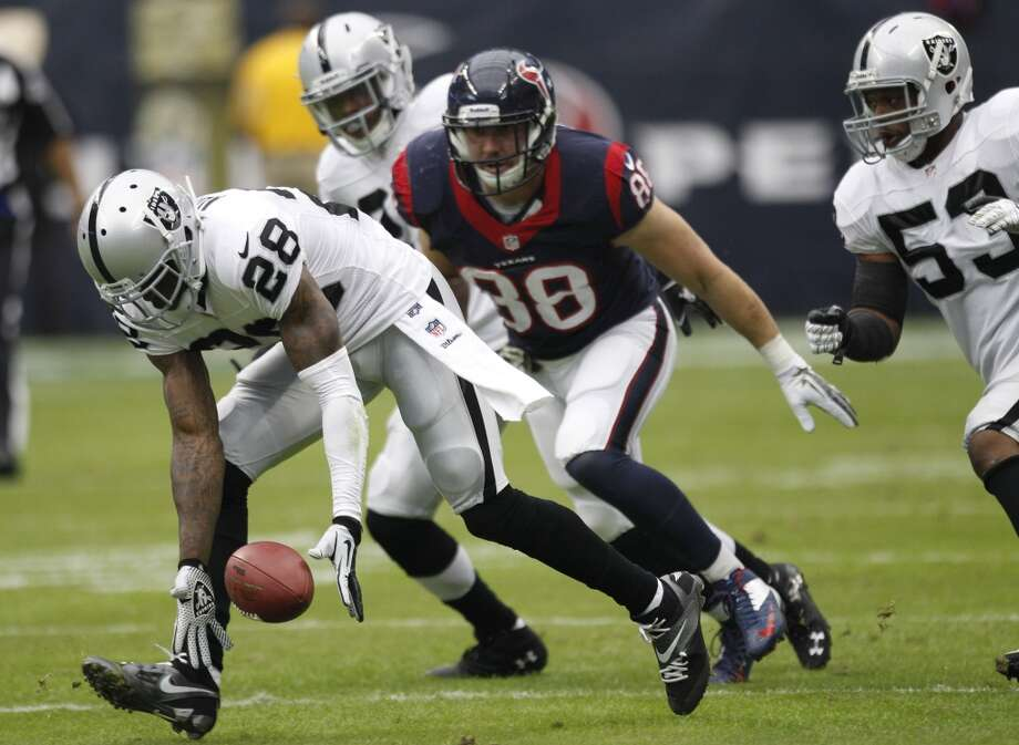 Raiders cornerback Phillip Adams picks up a fumble by Texans tight end Garrett Graham on the game's opening drive. Photo: Brett Coomer, Houston Chronicle