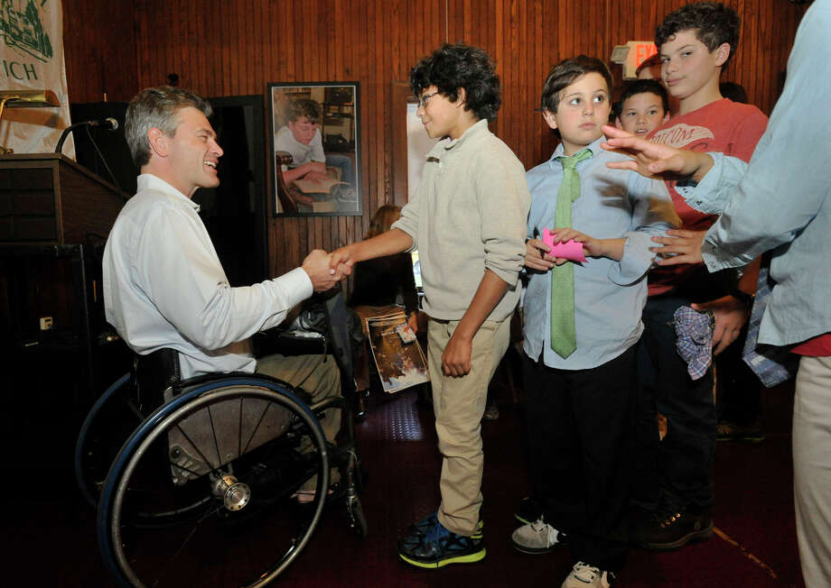 Max Johns, 13, is the first in line to talk with Chris Waddell, left, a paralympic skiier who also climbed Mount Kilimanjaro, after Waddell spoke to students at Eagle Hill School in Greenwich, Conn., on Monday, Nov. 18, 2013. Photo: Jason Rearick / Stamford Advocate