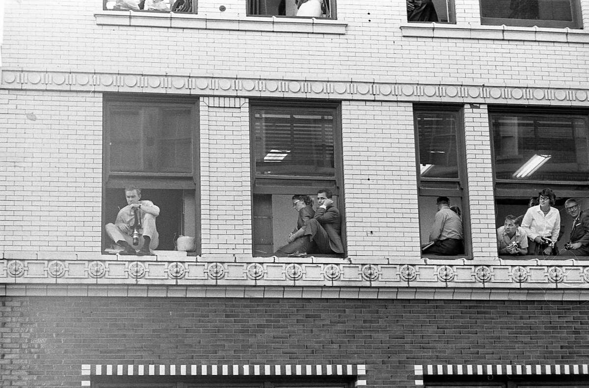Houston Chronicle staffers look out the windows of the Chronicle building to catch a glimpse of President John F. Kennedy and his motorcade arriving at the Rice Hotel across the street on Nov. 21, 1963.