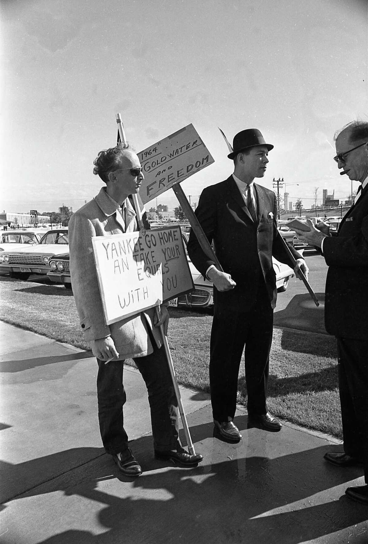 Dallas protesters with anti-Kennedy placards await the arrival of President John F. Kennedy.