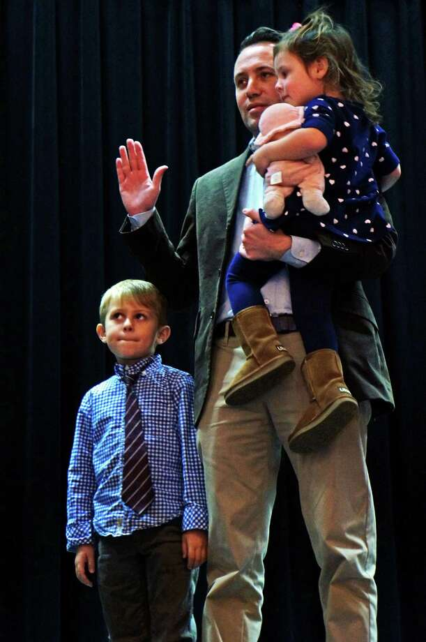Keith Varian brought his children on stage Monday night as he took the oath of office for Representative Town Meeting District 2. Photo: Genevieve Reilly / Fairfield Citizen