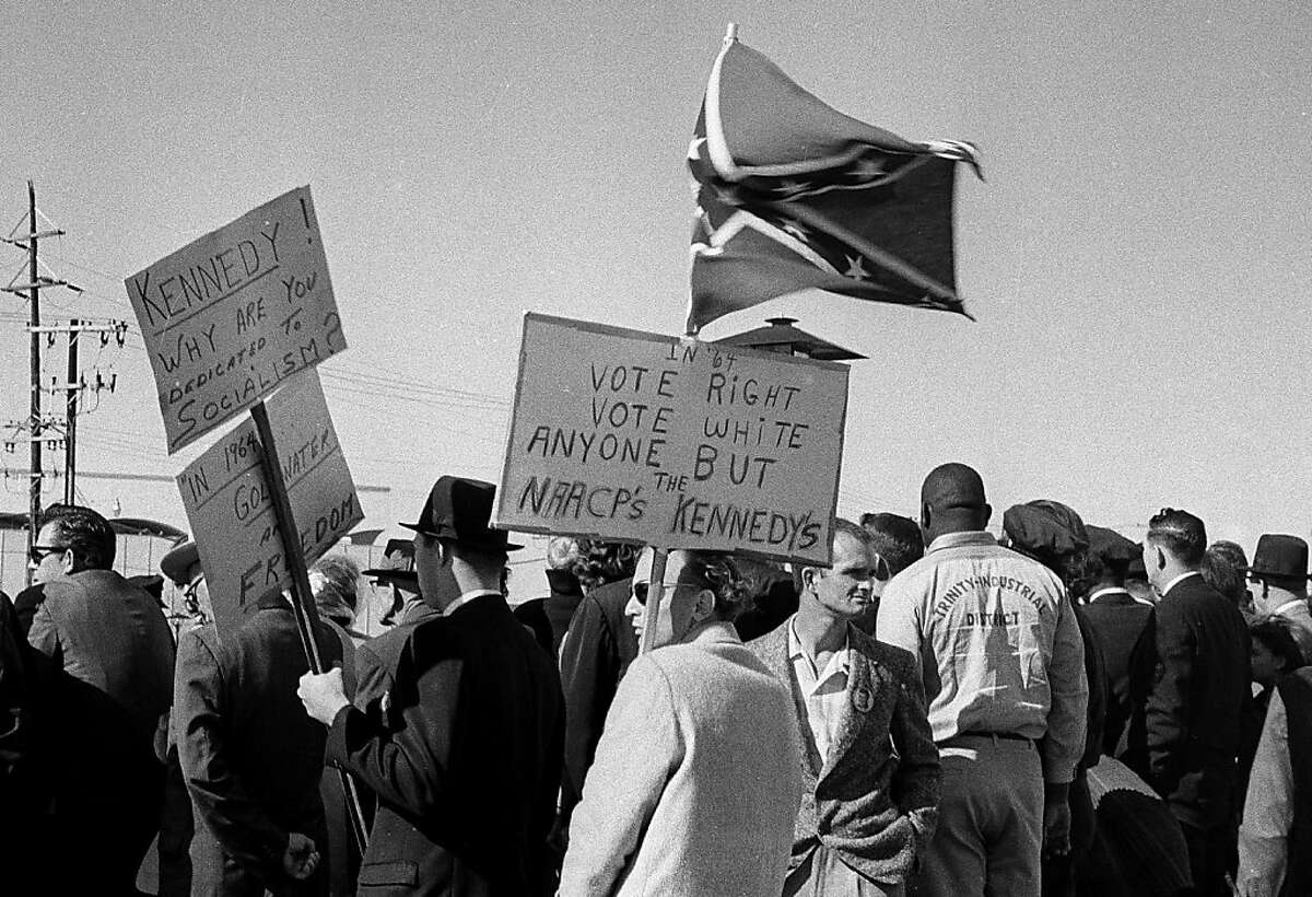 ADVANCE FOR USE SUNDAY, JULY 14, 2013 AND THEREAFTER - FILE - In this Nov. 22, 1963 file photo, people, including right-wing protesters carrying a Confederate flag and anti-Kennedy placards, await the arrival of President John F. Kennedy at Love Field in Dallas. The 50th anniversary of Kennedy's assassination throws a new spotlight on the deep hostility toward Kennedy that some Dallasites voiced before the assassination. (AP Photo/File)