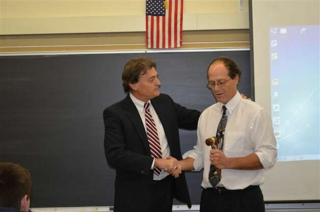 Senior Colonie Town Justice and Court Administrator Peter G. Crummey presents his seventh annual Gavel Award to Shaker High School business law teacher Chad Finck during a surprise visit to one of Finck's classes on Nov. 14. Finck, in his 26 years of teaching at Shaker, has taught a variety of subject areas and has conducted in-depth looks at court systems with his students.