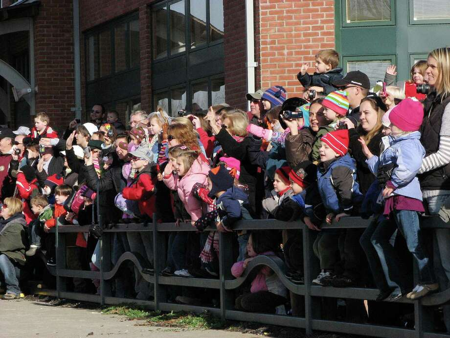 Families watch as the Canadian Pacific Holiday Train pulls into the Amtrak Train Station in Saratoga Springs on Monday, Nov. 29, 2010.  The train makes stops at communities along the rail lines in the United States and in Canada, and those coming out to see the train are encouraged to bring canned goods to help stock the shelves of their local food pantry.   The Holiday Train started in 1999,  and more than 4.8 million in cash and over 2.3 million pounds of food have been collected in Canada and the United States.  (Paul Buckowski / Times Union) Photo: Paul Buckowski / 00010931A