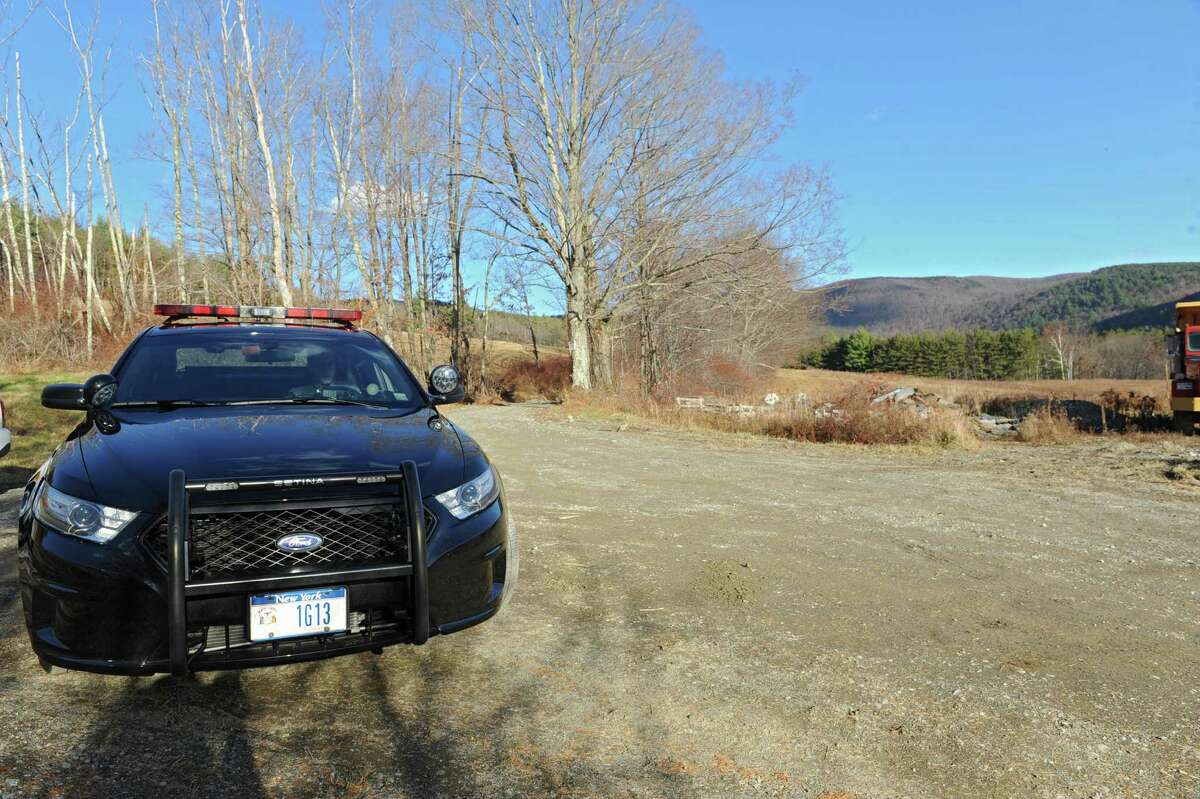 A New York State trooper is parked at a road block on Cowdry Hollow Road not too far from a investigation scene on Monday, Nov. 18, 2013 in Berlin, N.Y. Troopers shot and killed a Berlin man after he allegedly made a motion as if he was lifting a weapon. (Lori Van Buren / Times Union)
