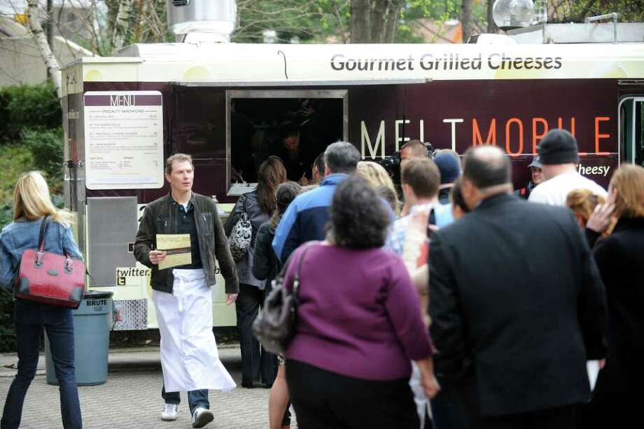 Bobby Flay makes menus available to the crowd at MELT Mobile, a food truck stationed at Veterans Park on Atlantic Street in Stamford, Conn. on Thursday, March 29, 2012. Photo: Cathy Zuraw / Stamford Advocate