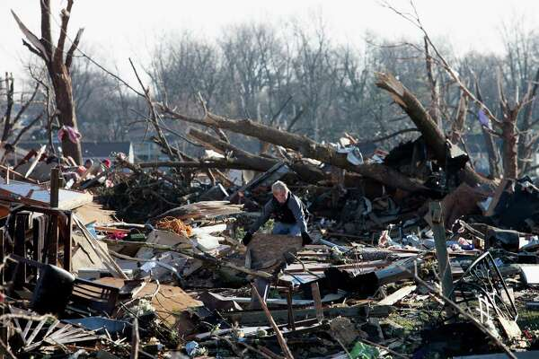 A resident searches through the debris of a home in Washington, Ill., Monday, Nov. 18, 2013, that was destroyed by a tornado the day before in this central Illinois town. The unusually powerful late-season wave of thunderstorms brought damaging winds and tornadoes to 12 states. Illinois was the hardest hit. The tornado damaged or destroyed as many as 500 homes in the town. (AP Photo/Armando Sanchez)