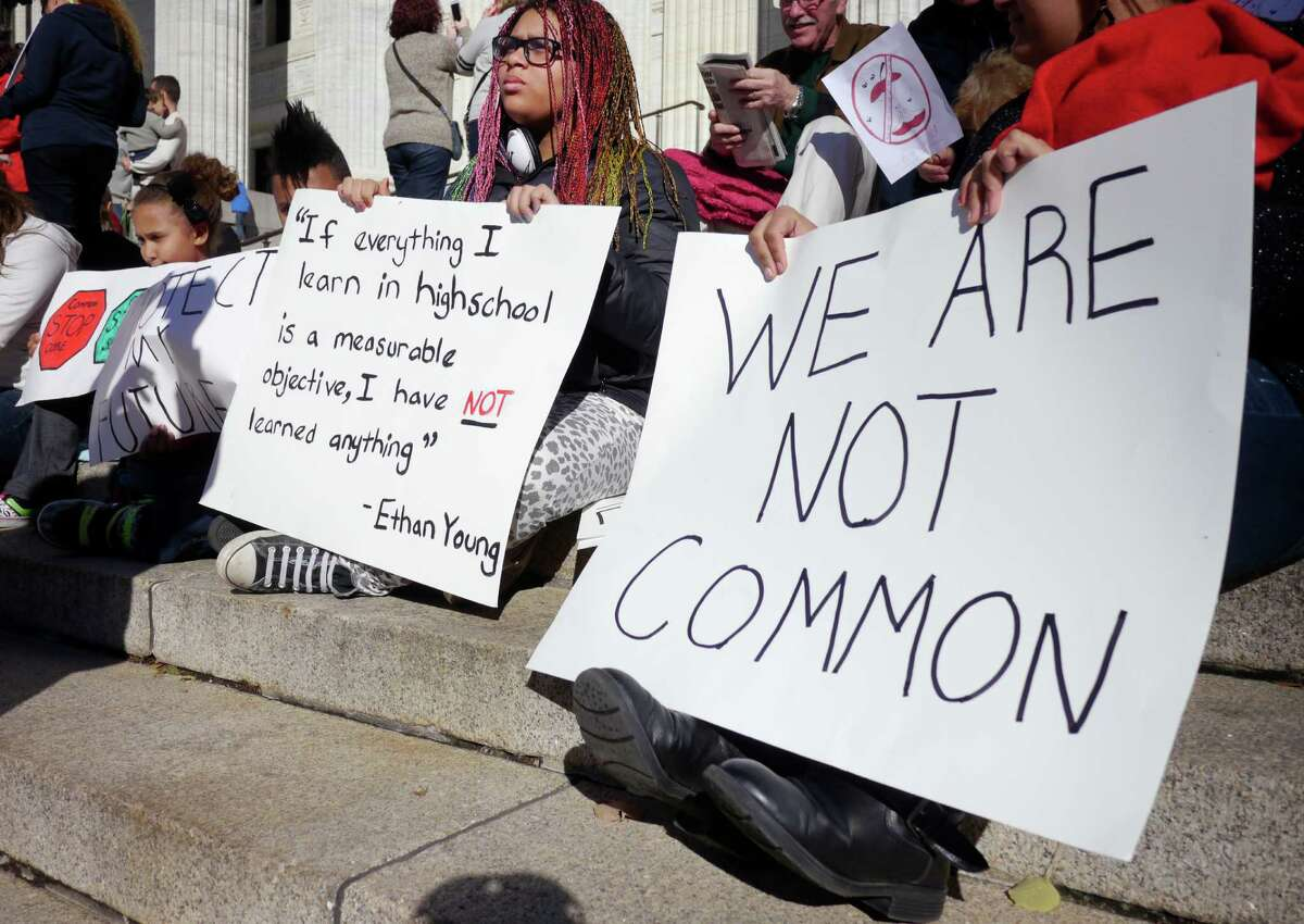D'Ana Blair, center, 13, takes part in an event held by parents and students outside the State Education building to protest the implementation of the Common Core set of educational standards in New York's schools on Monday, Nov. 18, 2013 in Albany, NY. Blair said that she is struggling in math under the Common Core and that the tutors at the Mechanicville Junior High School are overwhelmed with students needing extra help. Blair feels that she is being left behind. (Paul Buckowski / Times Union)