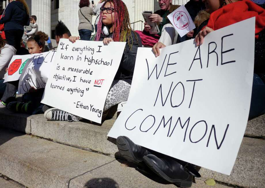 D'Ana Blair, center, 13,  takes part in an event held by parents and students outside the State Education building to protest the implementation of the Common Core set of educational standards in New York's schools on Monday, Nov. 18, 2013 in Albany, NY.  Blair said that she is struggling in math under the Common Core and that the tutors at the Mechanicville Junior High School are overwhelmed with students needing extra help.  Blair feels that she is being left behind.   (Paul Buckowski / Times Union) Photo: Paul Buckowski / 00024683A