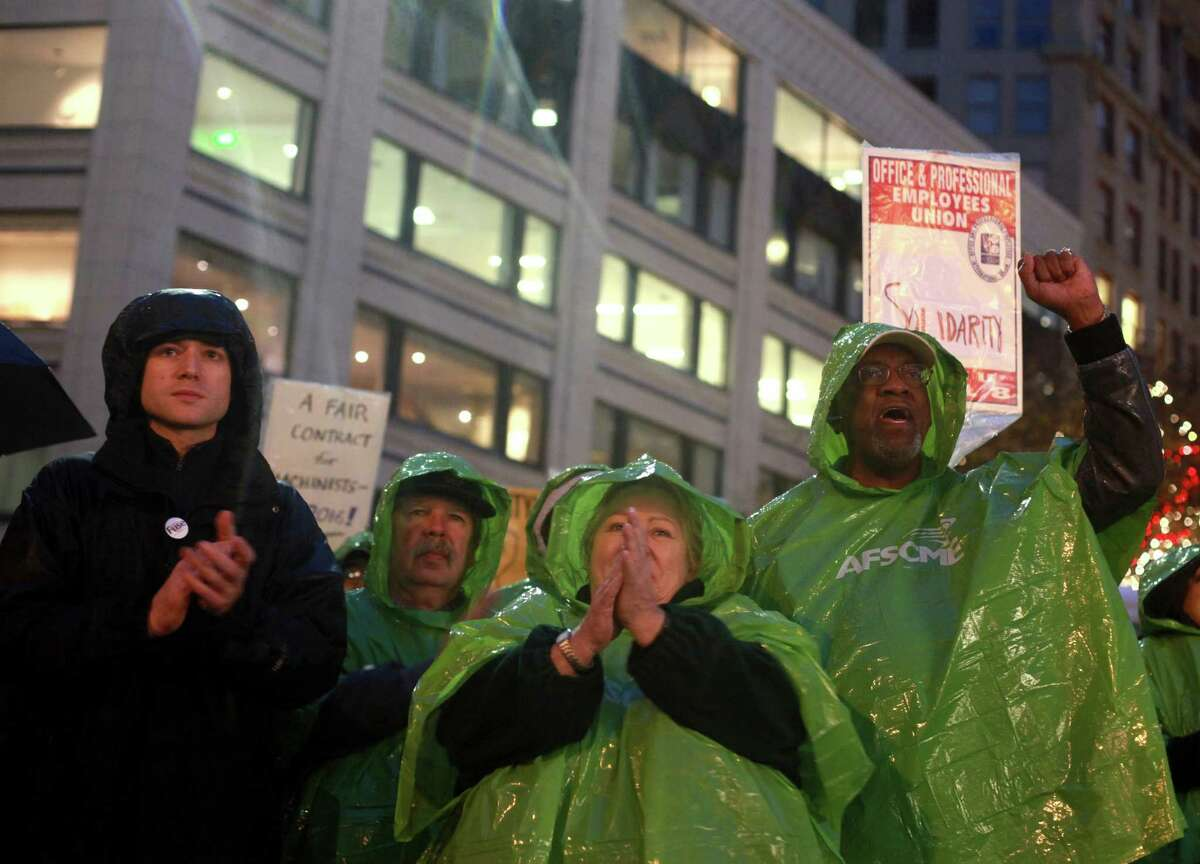 Julianne Moore and Claude Burfect, members of the American Federation State County Municipal Employees Union, are shown wearing green ponchos at the Community & Labor Rally at Westlake Park on Monday, Nov. 18, 2013. The rally was held to support union members that voted against a contract offered by Boeing. The decision by the Machinists Union may lead to Boeing building the 777X outside of Washington state.