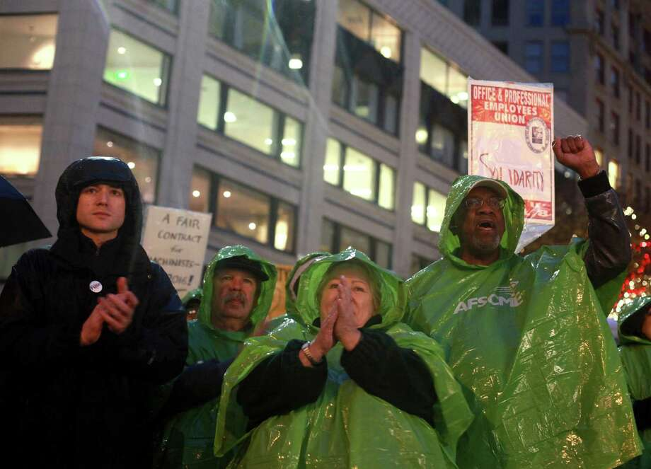 Julianne Moore and Claude Burfect, members of the American Federation State County Municipal Employees Union, are shown wearing green ponchos at the Community & Labor Rally at Westlake Park on Monday, Nov. 18, 2013. The rally was held to support union members that voted against a contract offered by Boeing. The decision by the Machinists Union may lead to Boeing building the 777X outside of Washington state. Photo: SOFIA JARAMILLO, SEATTLEPI.COM / SEATTLEPI.COM