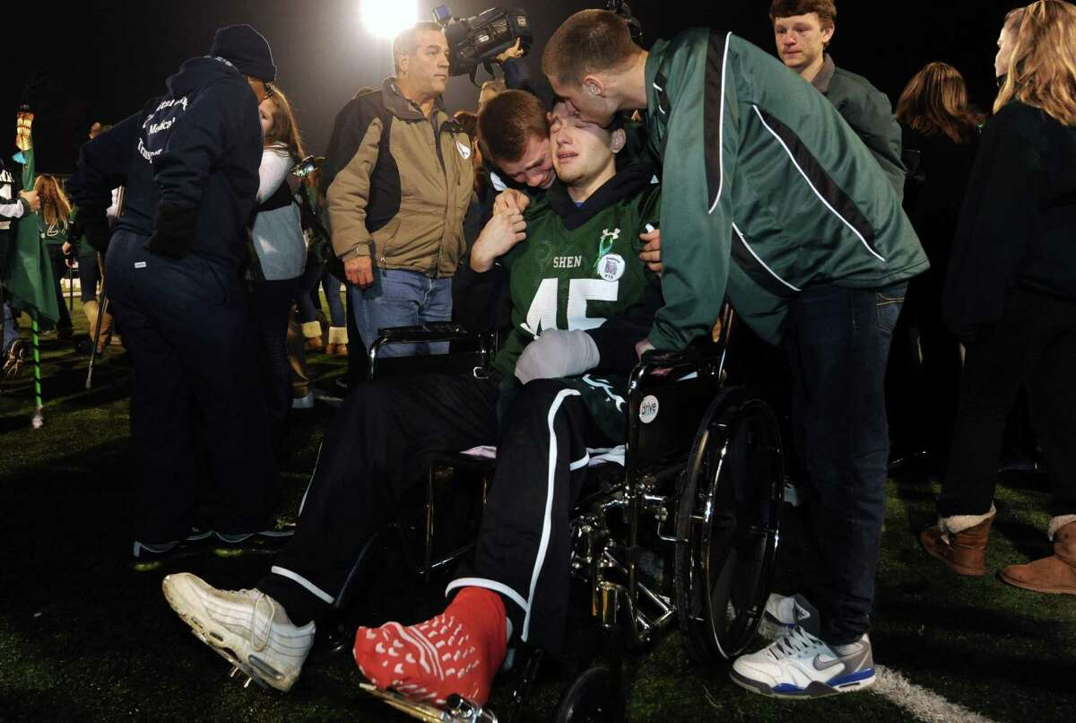 Crash survivor Matt Hardy, center, is greeted by football teammates after arriving by medical van during a candlelight vigil and memorial service for the Shen crash victims at Shenendehowa High School in Clifton Park, NY Tuesday Dec. 4, 2012. Shen students Chris Stewart and Deanna Rivers died in the crash with Matt Hardy and Bailey Wind being seriously injured.(Michael P. Farrell/Times Union)