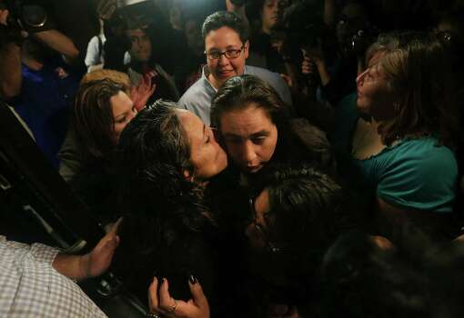Cassandra Rivera, center left, kisses Anna Vasquez as Rivera, Kristie Mayhugh, above, and Elizabeth Ramirez, below, are released from prison at The Bexar County Jail, Monday, Nov. 18, 2013. Anna Vasquez, was released on parole from prison just over a year ago. Photo: Bob Owen, San Antonio Express-News / ©2013 San Antonio Express-News