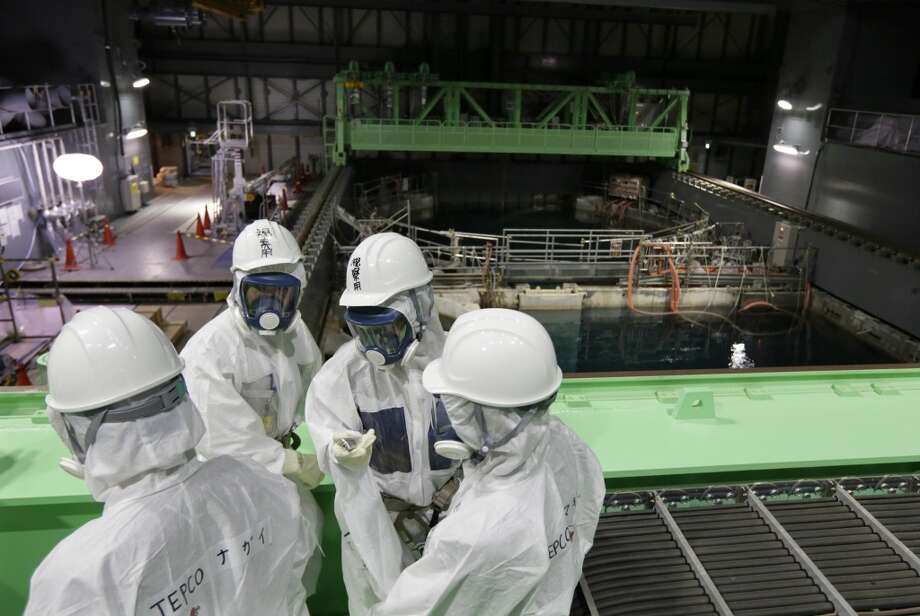 In this Nov. 7, 2013 file photo, Tokyo Electric Power Co. (TEPCO) employees and journalists wearing protective suits and masks look at the spent fuel pool inside the building housing the Unit 4 reactor at the Fukushima Dai-ichi nuclear power plant in Okuma town, Fukushima prefecture, northeastern Japan.  Workers started the difficult task Monday, Nov. 18, 2013,  of removing nuclear fuel rods from a heavily-damaged reactor building at the Fukushima Dai-Ichi nuclear power plant in Japan. It's the first major step toward decommissioning the plant, a decades-long process fraught with uncertainty and challenges. Photo: Kimimasa Mayama, ASSOCIATED PRESS