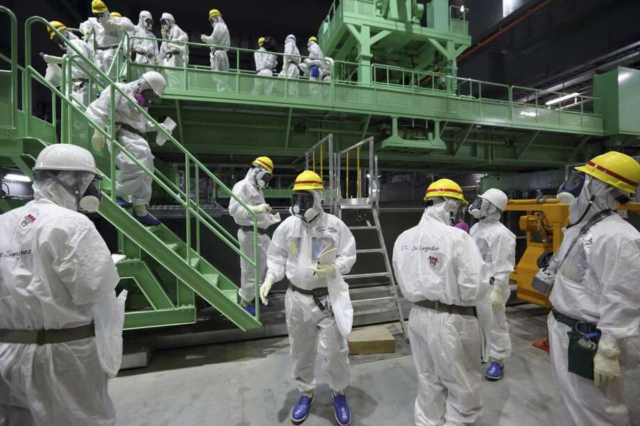 In this Nov. 7, 2013 file photo, members of the media and Tokyo Electric Power Co. employees wearing protective suits and masks walk down the steps of a fuel handling machine after looking at the spent fuel pool inside the building housing the Unit 4 reactor at the Fukushima Dai-ichi nuclear power plant in Okuma, Fukushima Prefecture, Japan. Workers will begin removing radioactive fuel rods Monday from one of four reactors at the crippled Fukushima Dai-Ichi nuclear power plant, Tokyo Electric Power Co. said. The painstaking and risky task is a crucial first step toward a full cleanup of the earthquake and tsunami-damaged plant in northeastern Japan. Photo: Tomohiro Ohsumi, ASSOCIATED PRESS