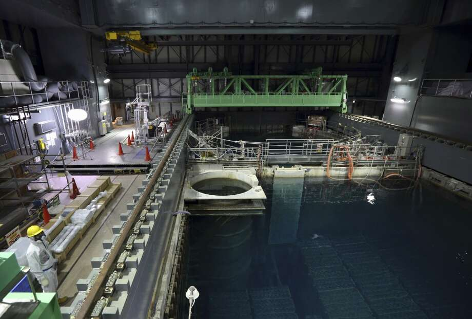 In this Nov. 7, 2013 file photo, a Tokyo Electric Power Co. employee wearing a protective suit and a mask stands next to the spent fuel pool inside the building housing the Unit 4 reactor at the Fukushima Dai-ichi nuclear power plant in Okuma, Fukushima Prefecture, Japan. Workers will begin removing radioactive fuel rods Monday, Nov. 18, 2013,  from one of four reactors at the crippled Fukushima Dai-Ichi nuclear power plant, Tokyo Electric Power Co. said. The painstaking and risky task is a crucial first step toward a full cleanup of the earthquake and tsunami-damaged plant in northeastern Japan. Photo: Tomohiro Ohsumi, ASSOCIATED PRESS