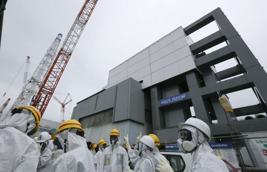 In this Nov. 7, 2013 file photo, journalists and Tokyo Electric Power Co. employees wearing protective suits and masks stand outside the Unit 4 reactor building before starting their inspection at the Fukushima Dai-ichi nuclear power plant in Okuma town, Fukushima prefecture, northeastern Japan. Workers will begin removing radioactive fuel rods Monday, Nov. 18, 2013,  from one of four reactors at the crippled Fukushima Dai-Ichi nuclear power plant, Tokyo Electric Power Co. said. The painstaking and risky task is a crucial first step toward a full cleanup of the earthquake and tsunami-damaged plant in northeastern Japan. Photo: Kimimasa Mayama, ASSOCIATED PRESS