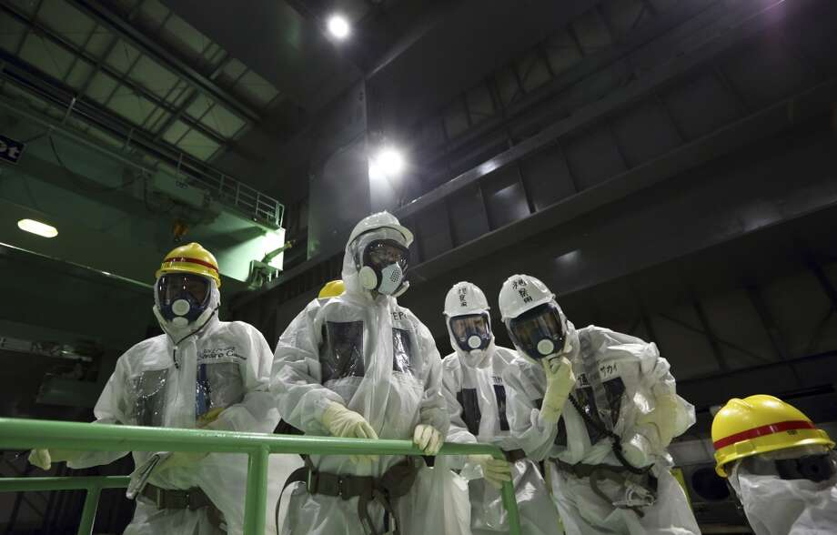 In this Nov. 7, 2013 file photo, members of the media wearing protective suits and masks look at the spent fuel pool from a fuel handling machine inside the building housing the Unit 4 reactor at the Fukushima Dai-ichi nuclear power plant in Okuma, Fukushima Prefecture, Japan. Workers will begin removing radioactive fuel rods Monday, Nov.18, 2013,  from one of four reactors at the crippled Fukushima Dai-Ichi nuclear power plant, Tokyo Electric Power Co. said. The painstaking and risky task is a crucial first step toward a full cleanup of the earthquake and tsunami-damaged plant in northeastern Japan. Photo: Tomohiro Ohsumi, ASSOCIATED PRESS