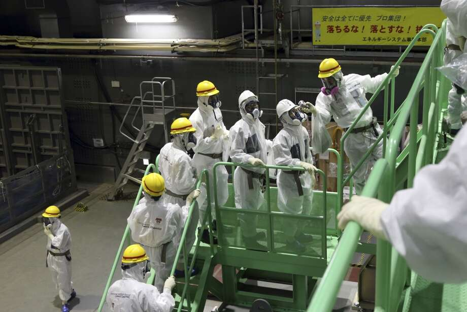 Members of the media and Tokyo Electric Power Co. employees wearing protective suits and masks walk up the steps of a spent fuel handling machine as they look at the spent fuel pool inside the building housing the Unit 4 reactor at the Fukushima Dai-ichi nuclear power plant in Okuma, Fukushima, northeastern Japan, Thursday, Nov. 7, 2013. Japanese regulators on Oct. 30 formally approved the removal of fuel rods from the cooling pool at the damaged Unit 4 reactor building considered the highest risk at the crippled nuclear plant. Removing the fuel rods is the first major step in a decommissioning process that is expected to last decades at the Fukushima plant, where three reactors melted down after the March 2011 earthquake and tsunami. Photo: Tomohiro Ohsumi, ASSOCIATED PRESS
