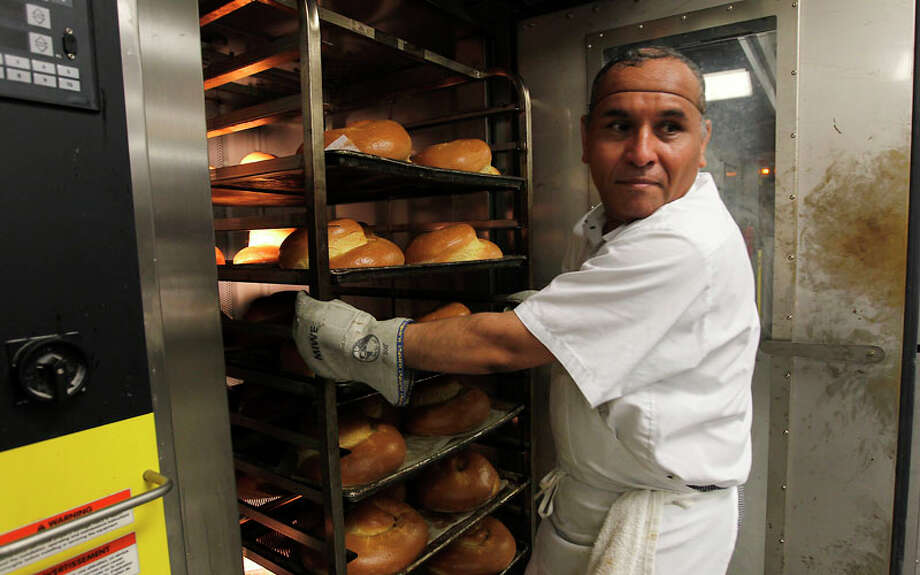 Eduardo Sanchez pulls freshly baked challahs out of the oven at Three Brothers Bakery. Photo: Karen Warren, Houston Chronicle / © 2011 Houston Chronicle