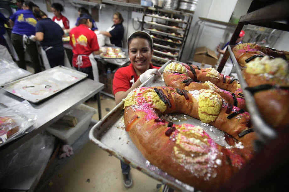 "Kira Aruvizo gets ready to box ""Roscas"" or Kings Bread, a doughnut shaped bread with a plastic baby Jesus hidden inside, families share the bread as they celebrate El Dia de los Reyes Magos or Three Kings Day at El Bolillo Bakery. Photo: Mayra Beltran, Houston Chronicle / © 2011 Houston Chronicle"