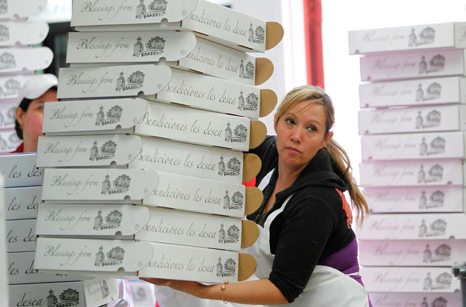 "Alma Torres carries assembled packages to box the ""Roscas"" or Kings Bread at El Bolillo Bakery. Photo: Mayra Beltran, Houston Chronicle / © 2011 Houston Chronicle"