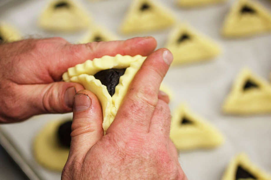 Bobby Jucker folds a Chocolate hamentashen, triangular pastries traditionally made for the Jewish holiday of Purim, at Three Brothers Bakery. Photo: Michael Paulsen, Houston Chronicle / © 2012 Houston Chronicle