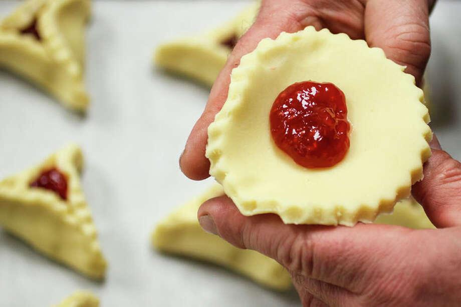 Bobby Jucker folds a Raspberry hamentashen at Three Brothers Bakery. Photo: Michael Paulsen, Houston Chronicle / © 2012 Houston Chronicle