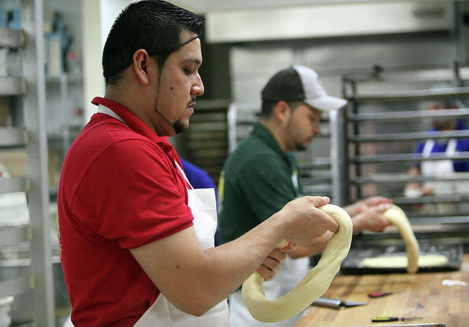 Premitivo Ortero gives the 'Roscas de Reyes' or Kings Bread its round shape at El Bolillo Bakery. Photo: Mayra Beltran, Houston Chronicle / © 2012 Houston Chronicle