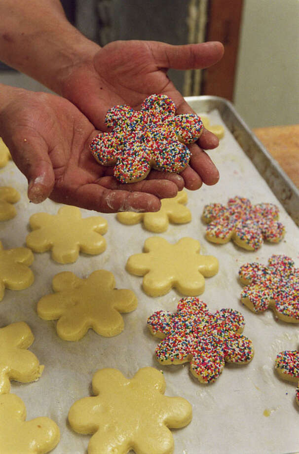 A cook in the El Bolillo bakery on Airline holds a cookie decorated with colored sugar decorations. Photo: Steve Campbell, Houston Chronicle / Houston Chronicle