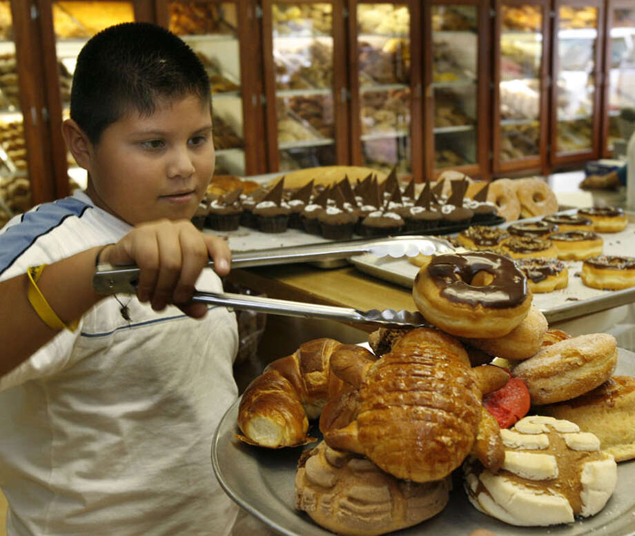 Juan Jose Cano Meza loads up on  a variety  of Mexican baked goods as he purchases bread at El Bolillo. Photo: Carlos Antonio Rios, Houston Chronicle / Houston Chronicle