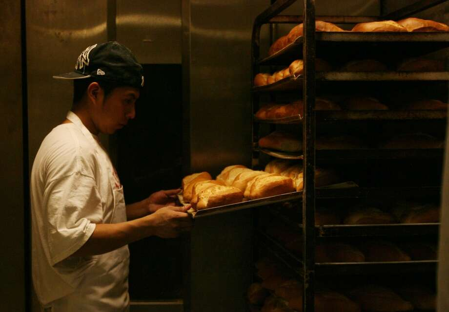 Juan Carlos Lopez checks if bread has cooled down at El Bolillo Bakery. Photo: Mayra Beltran, Houston Chronicle