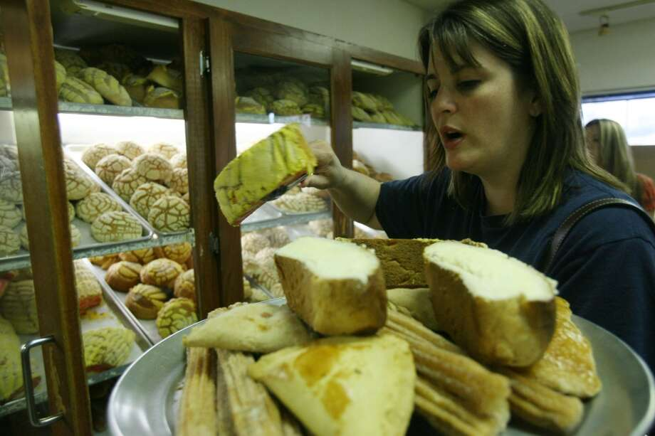 Landa Harcourt buys fresh baked bread at El Bolillo Bakery. Photo: Mayra Beltran, Houston Chronicle