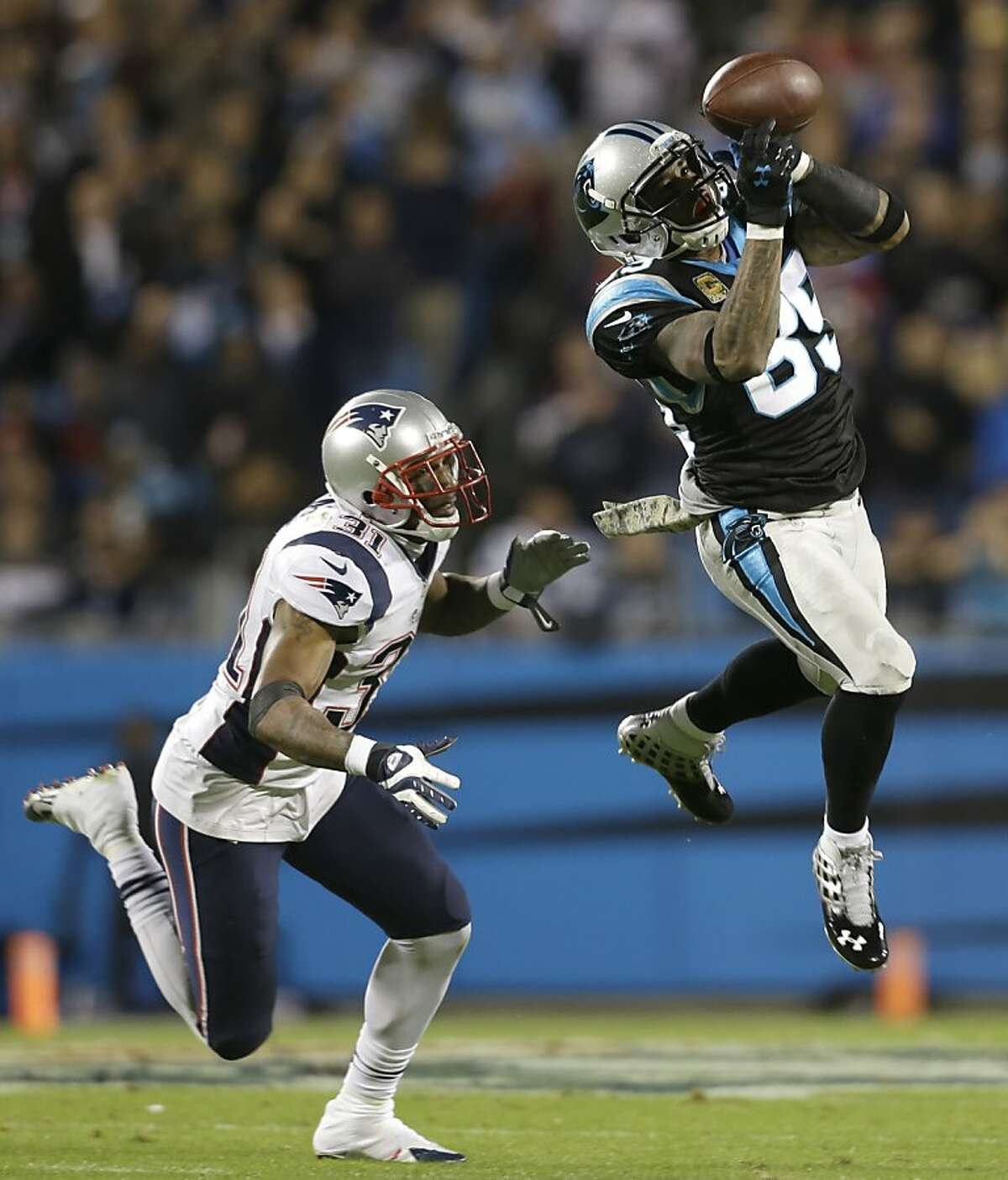 Carolina Panthers' Steve Smith (89) catches a pass as New England Patriots' Aqib Talib (31) defends during the first half of an NFL football game in Charlotte, N.C., Monday, Nov. 18, 2013.