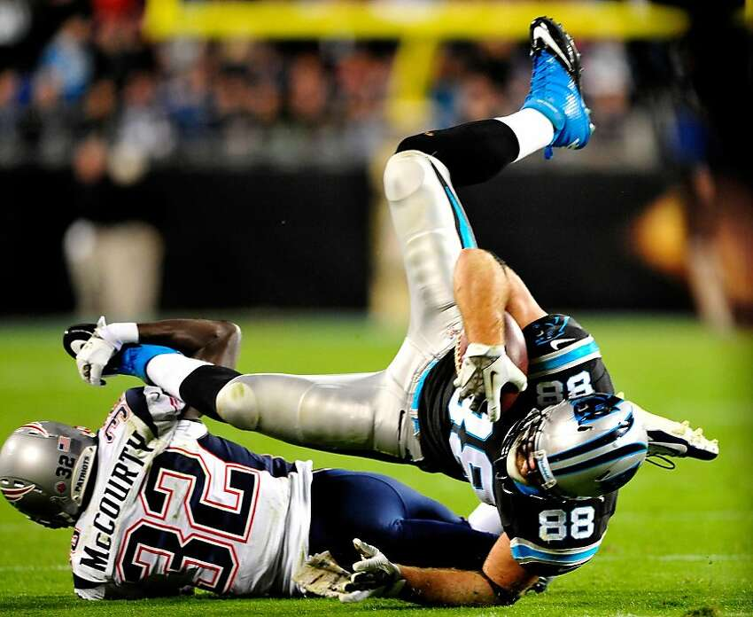 Devin McCourty #32 of the New England Patriots upends Greg Olsen #88 of the Carolina Panthers during play at Bank of America Stadium on November 18, 2013 in Charlotte, North Carolina. The Panthers won 24-20.