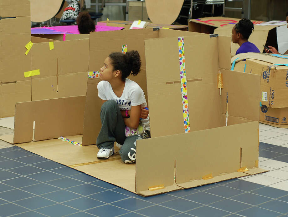 Kingwood Park High School student Jaelynn Johnson huddles in her cardboard shelter, part of the Cardboard City project in the Humble school district. Constructed at Atascocita High, the project was a symbol of compassion for the homeless. Photo: Courtesy HISD