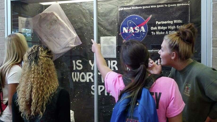 Oak Ridge High students Kayli Anthony, left, Shawntavia Davis, Tessa Diller and Taylor Clemens admire a display of a bag created by the Oak Ridge High School's Students United with NASA to Create Hardware. The bag had been used by NASA in space. Photo: Courtesy