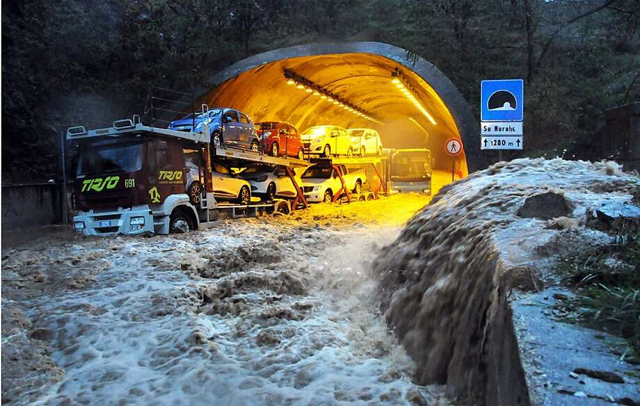 'Apocalyptic storm': Rushing water strands a truck and a bus in a tunnel near Olbia, Sardinia. The Mediterranean island began to clean up after a freak torrential rainstorm killed at least 18 people, downed bridges and swept away cars. Photo: Massimo Locci, Associated Press