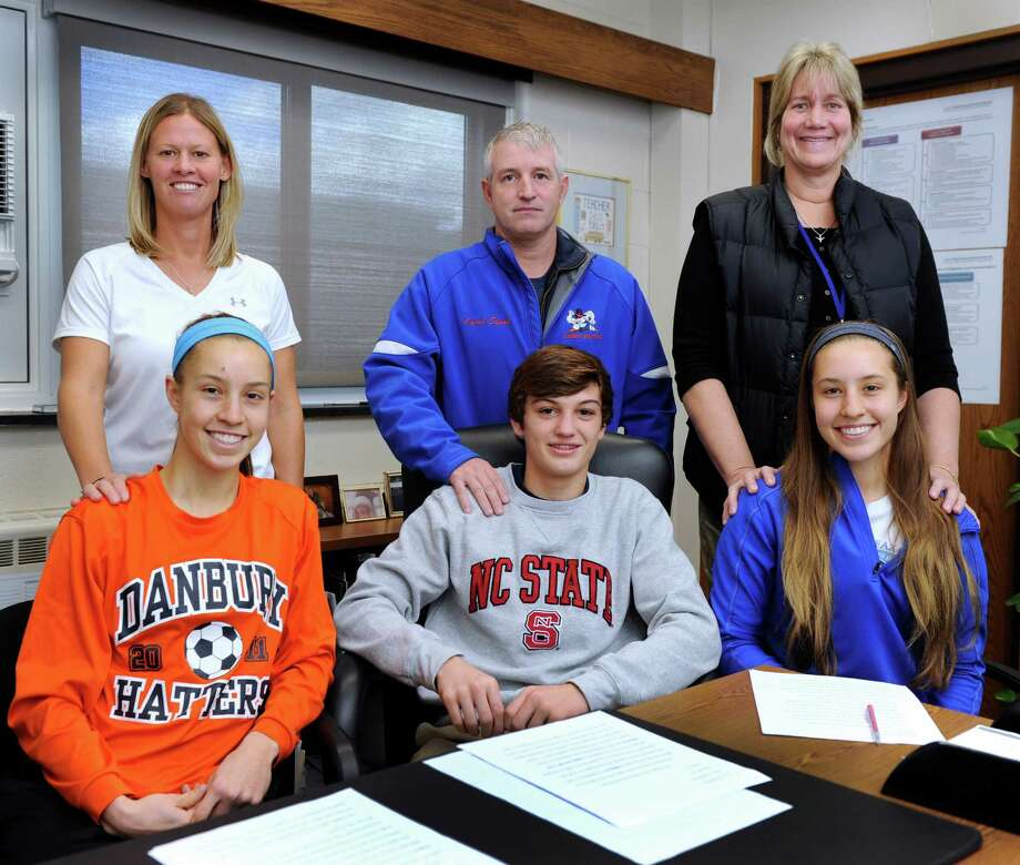 Three Danbury High School athletes are signing national letters of intent to play sports in college, Tuesday, Nov. 19, 2013, in Danbury, Conn. They are photographed with their coaches, from left, Rebecca Gartner with soccer coach Jessica Halas, Kevin Jack, 17, with wrestling coach Ricky Shook and Rachel Gartner, 17, with girls basketball coach, Jackie DiNardo. Photo: Carol Kaliff / The News-Times