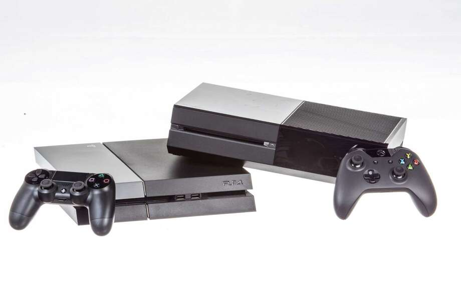 The Sony Playstation 4, at left, and the Microsoft XBox One, in New York, Nov. 12, 2013. The new consoles are vying to be an all-in-one conduit for entertainment content into living rooms, even as competition for the time of both gamers and TV-watchers proliferates. (Tony Cenicola/The New York Times) ORG XMIT: XNYT140 Photo: TONY CENICOLA / NYTNS